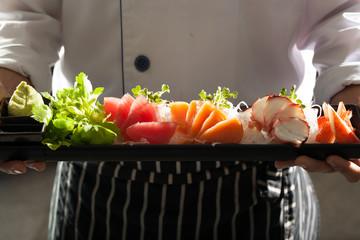 sashimi, a chef uniform holding a dish of Japanese Sashimi
