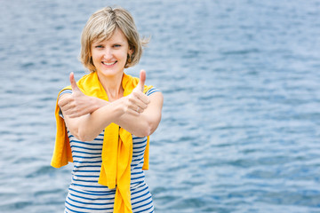 Middle age woman outdoors gesturing thumb up