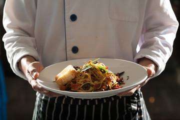 spaghetti, a chef uniform holding a dish of seafood spaghetti