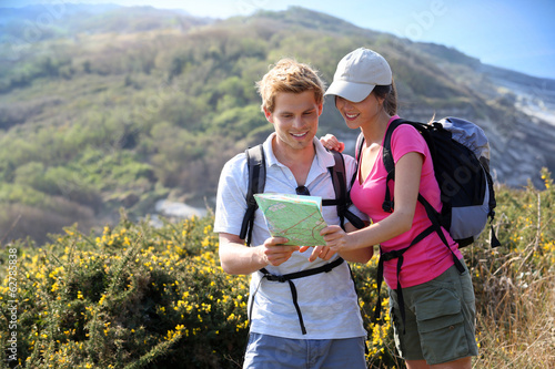 Hikers in country path looking at map