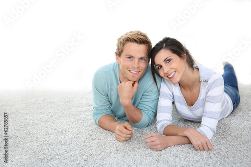 Cheerful young couple laying on carpet floor