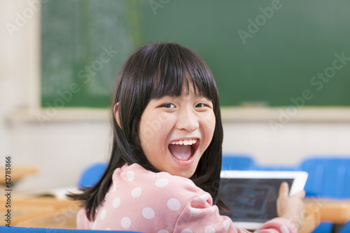 happy little schoolgirl holding digital tablet at desk