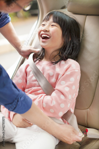 father take care daughter to fasten a seat belt