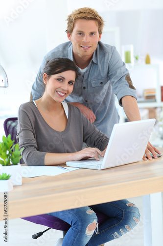 Young people in office working on laptop