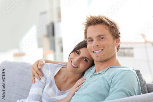 Smiling young couple relaxing in sofa at home