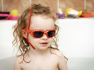 Little toddler playing in the bath with sunglasses