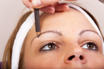 Kosmetikerin arbeitet mit einem Kajalstift
