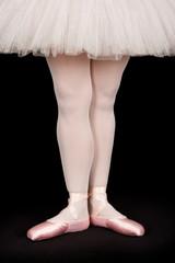 Ballet dancer standing on black floor while dancing artistic con