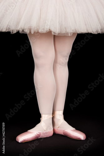 Ballet dancer standing on black floor while dancing artistic con