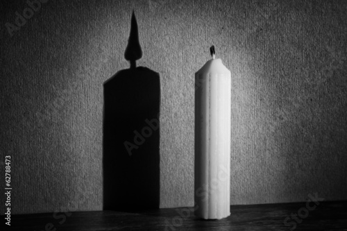 Candle in darkness with spotlight making shadow texture conversi
