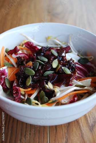 Spring salad in white bowl on wooden background