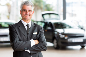senior car dealer principal standing in showroom
