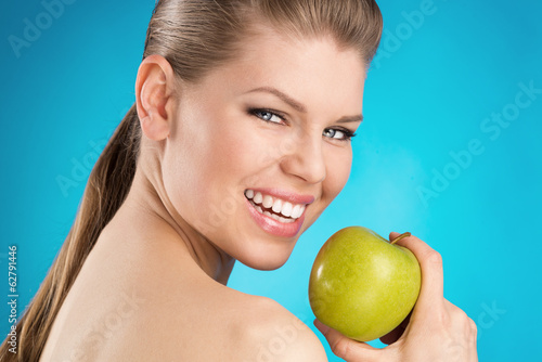 canvas print picture Healthy teeth protection. Young woman holding green apple