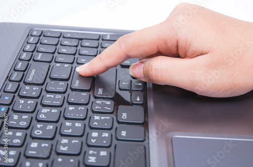 Closeup woman hand touch enter key