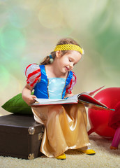 Smiling small girl sitting with a book and looking at pictures