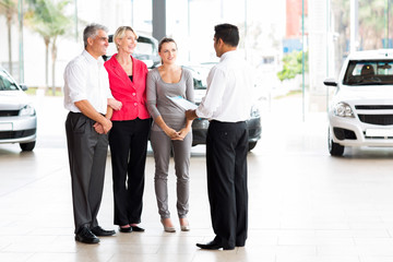 vehicle salesman explaining contract to family