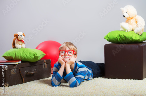 Portrait of a boy lying on the floor and thinking