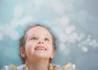 Portrait of a smiling cute girl looking up, abstract background