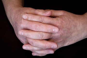 old hands crossing fingers