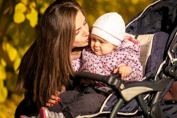 Closeup portrait of mother kissing daughter in buggy