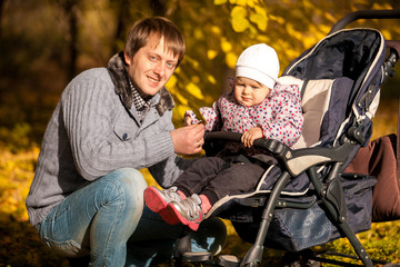 Portrait of young father and daughter in buggy at autumn park