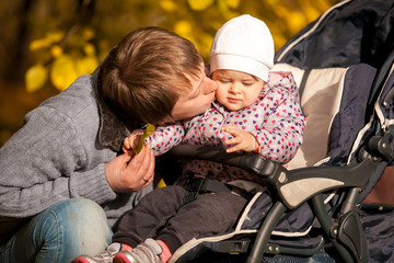 portrait of father kissing daughter sitting in buggy at park