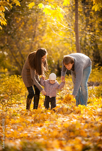 Young parents teaching small daughter to walk at autumn park