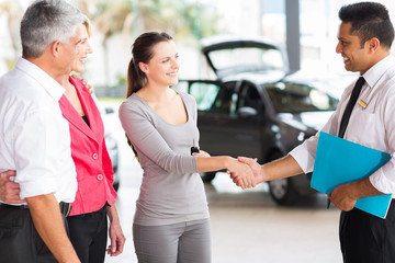 vehicle salesman handshake with young adult customer