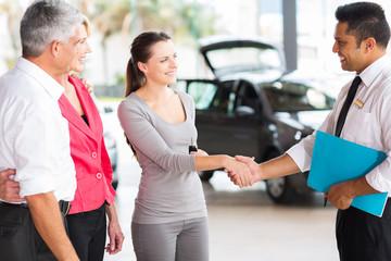 vehicle salesman handshake with young adult customer