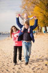 young family having fun on beach at autumn