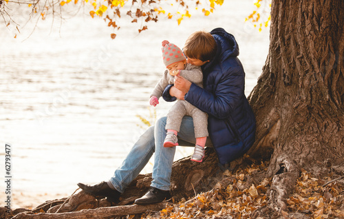 Young father relaxing under tree with small daughter