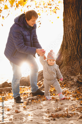 Outdoor photo of father and small daughter walking at riverbank