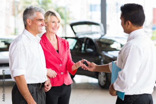 senior couple buying a new car