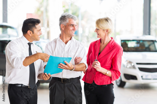 middle aged man talking to wife before buying a new car