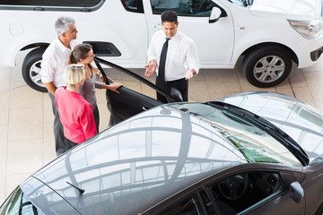 overhead view of car salesman showing vehicle to customers