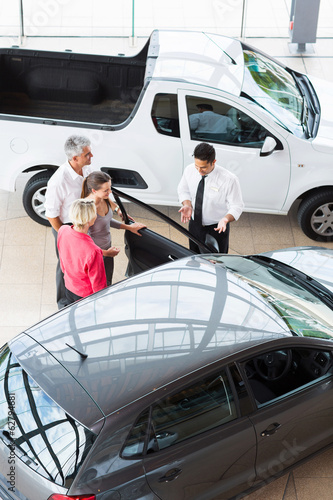 car dealer showing new car to customers