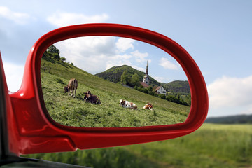 Landscape reflected in car rear view mirror