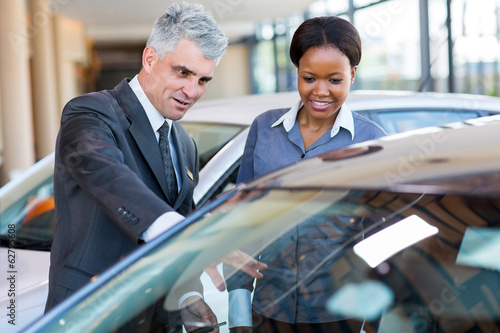 mature car dealer showing new car to african customer