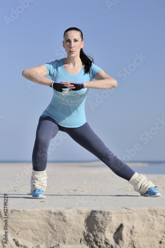 young woman doing workout on the beach