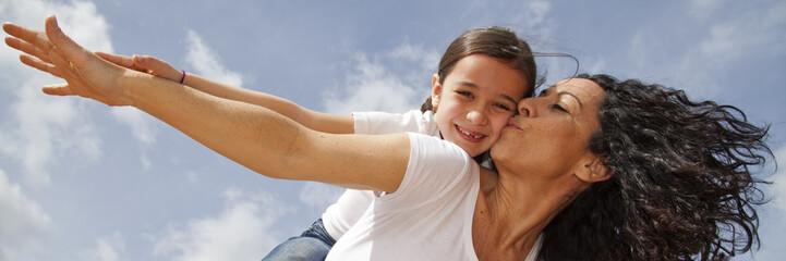 Madre besando a hija mientras juegan