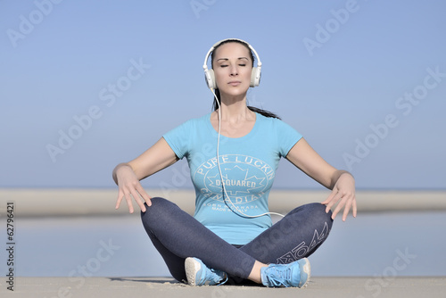 young woman listen to music on the beach