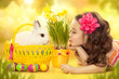 Happy little girl with easter rabbit and eggs