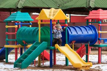 Beautiful happy kid on a winter playground outdoor