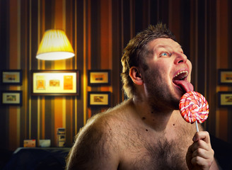 Crazy naked man licking lollipop indoors