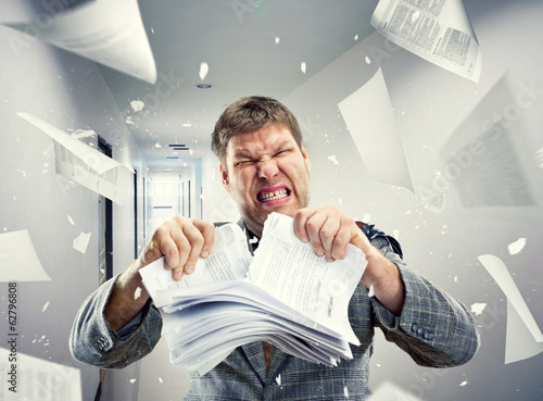Stressed businessman tearing out stack of paper at office