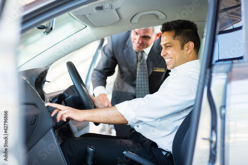 indian man checking car features at showroom