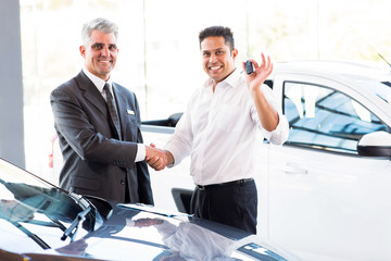 indian man showing new car key while handshaking with salesman
