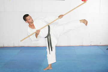 Man in shotokan karate with a bo in his hands
