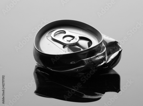 Crumpled beverage can on gray background