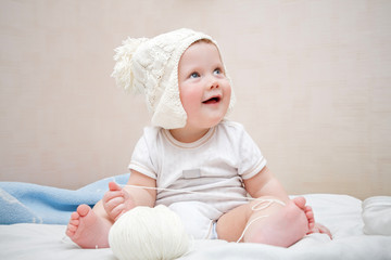 Cute baby in hat with pompom playing with yarn ball